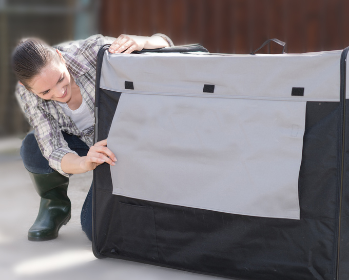 woman peeking thru a dog crate cover